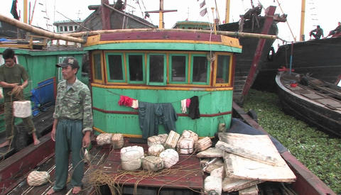 Fishing boats are moored at a dock, and fishermen prepare nets Footage