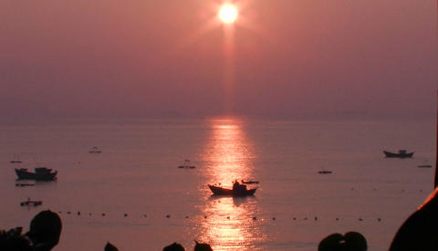 A small boat at sea at sunset in an Asian marina Stock Video Footage