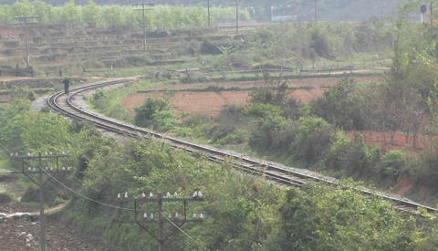 A man walks between railroad tracks at a bend Stock Video Footage