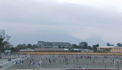 A large group of children play soccer in a schoolyard Stock Video Footage