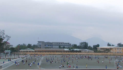 A large group of children play soccer in a schoolyard Footage
