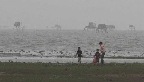 Two children and one adult digging in sand at a foggy... Stock Video Footage