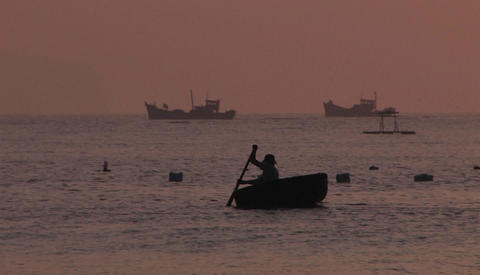 A man in a boat with ships in the background Stock Video Footage