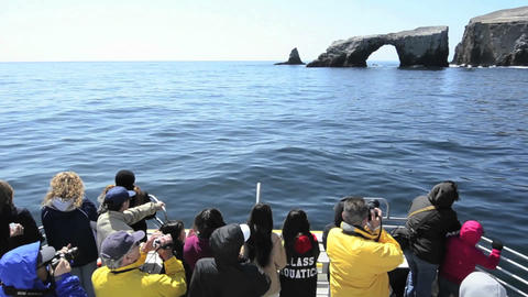 Sightseers on the bow of a boat approaching Anacap Stock Video Footage