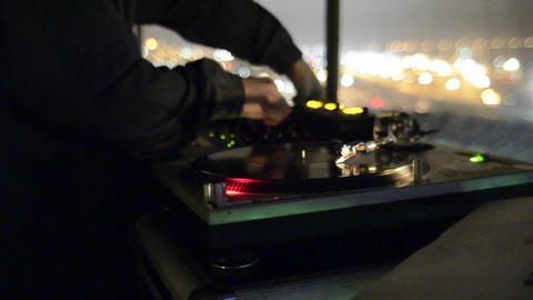 Rack focus on a disc Jockey spinning records and p Stock Video Footage