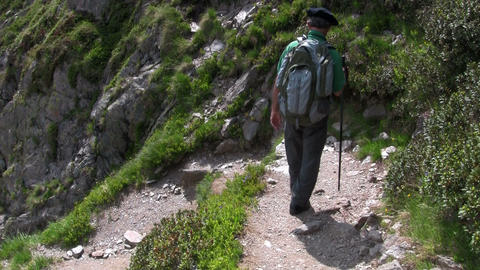 A man hikes down a mountain with a backpack Stock Video Footage