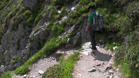 A man hikes down a mountain with a backpack Footage