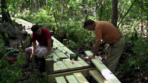 A father and son work on a wooden walkway through Stock Video Footage
