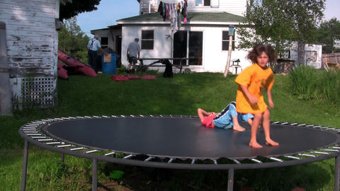 Kids jump and play on the trampoline in the backya Stock Video Footage