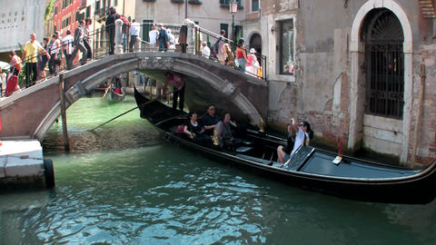 Gondolas take people through a narrow canal with b Stock Video Footage