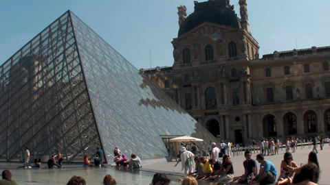 Crowds of people walk around the grounds of Louvre Stock Video Footage