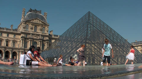People sit in front of the Louvre in Paris Stock Video Footage