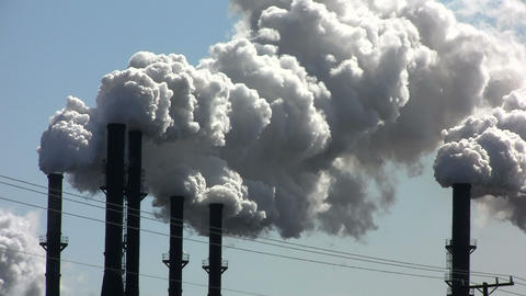 A power plant with smokestacks belches smoke into Stock Video Footage