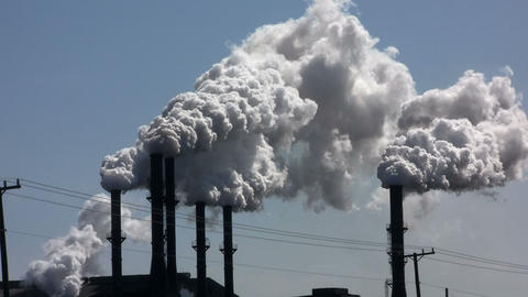 A power plant with smokestacks belches smoke into  Footage