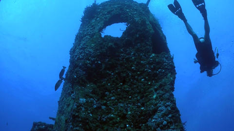 A diver swims around a shipwreck from a low angle Footage
