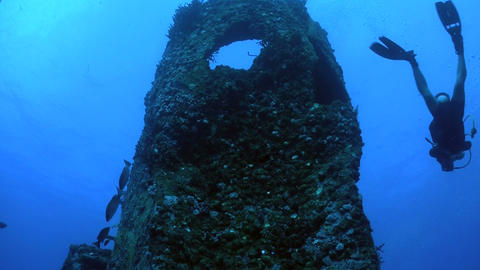 A diver swims around a shipwreck from a low angle Stock Video Footage