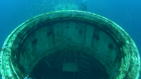 Divers swim around a shipwreck Stock Video Footage