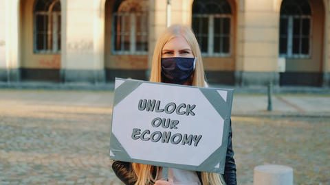 Young woman wearing medical mask calling to unlock the economy by holding Live Action