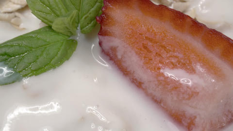 Oatmeal with yogurt and fresh strawberries close-up. Fresh mint. Extreme macro Live Action