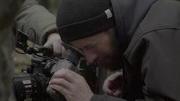 Cameraman looking through the viewfinder of the camera on shooting Footage