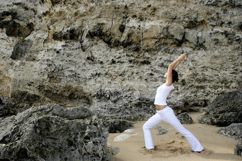 Young woman practicing yoga on the beach Foto