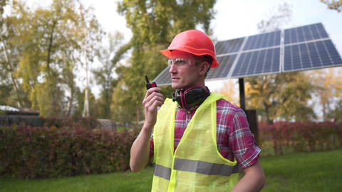 Engineer make call with walkie talkie in solar power plant. Power engineer at Live Action