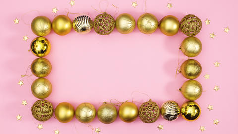 Gold Christmas ornament balls make frame with empty space inside and gold stars around Stop motion Live Action
