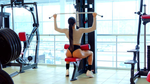 Athlete woman trains muscles of the back in the gym Footage