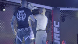 A break in the fight between rounds in the octagon . MMA Footage