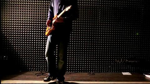 Guy Plays Guitar at Rehearsal in Dark Studio Footage