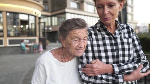 Nurse caring for elderly. Volunteer nurse hugs senior woman, smiles, is happy Live Action
