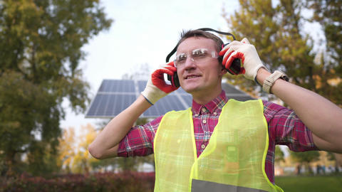 Man wearing hearing protection safety equipment at solar power station. Engineer Live Action