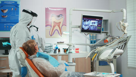 Dentist with face shield reviewing panoramic mouth x-ray image Live Action