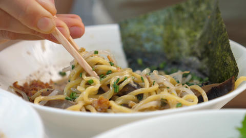 Trendy greasy Asian street food Close up of noodles from ramen soups hanging on the chopsticks Live Action