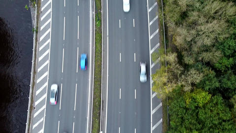 Aerial Overhead Drone Shot of UK Motorway flanked by Woods and River (2.7K) Live Action