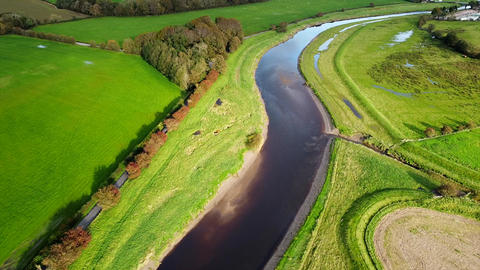 Aerial Drone Shot Over River Fields and Road Junction in UK Countryside (4K) Live Action