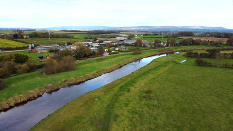 Overhead Aerial Drone Shot Flying Over River in Countryside by Farm Houses (4K) Live Action