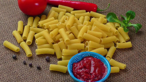 Raw yellow pasta, macaroni on sack background Footage