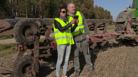 Farmers couple talking near tractor on field Footage