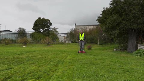 Worker pushing lawn mower Footage
