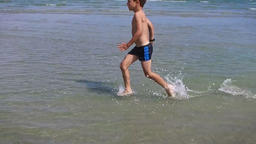 Little boy running in water at seaside, slow motion Footage