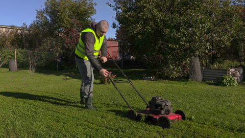 Worker talking on phone and pushing lawn mower Footage