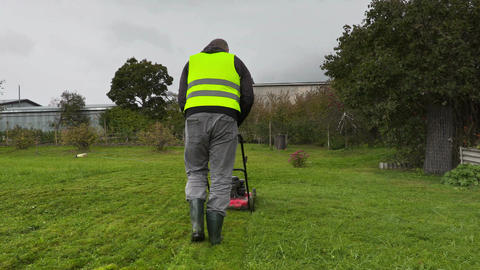 Worker starting cut the grass in rainy day Footage