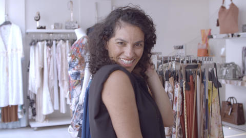 Cheerful Latin black haired woman posing in clothes shop Live Action