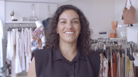 Friendly Latin black haired woman standing in clothes shop Live Action