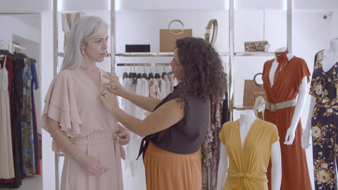Black haired shop assistant helping female customer Live Action