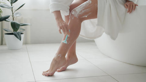 Low shot of woman shaving legs in bathroom using razor and cream caring for Live Action