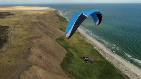 A man is paragliding over the seashore, beautiful landscape, sports Live Action