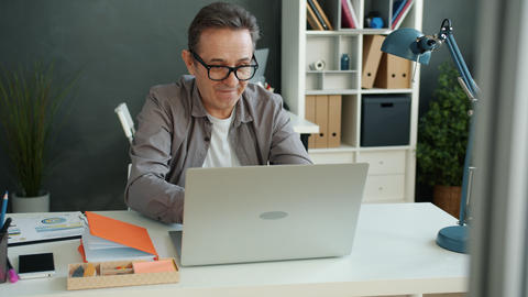 Emotional mature man working with laptop in office expressing negative emotions Live Action