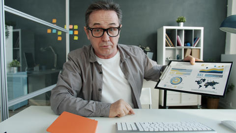Emotional mature office worker speaking showing charts during online video call Live Action